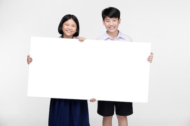 Enfants asiatiques mignons en uniforme d'étudiant avec tableau blanc.