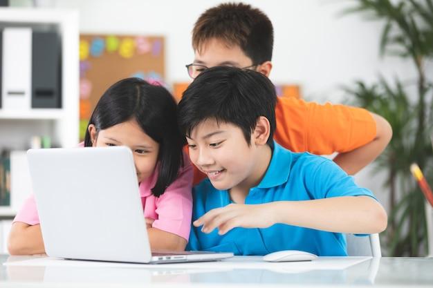 Enfants asiatiques mignons utilisant l'ordinateur portable ensemble.