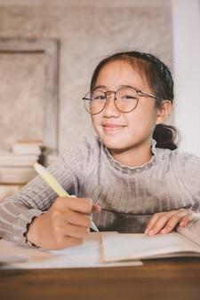 Enfants asiatiques portant des lunettes avec un stylo en main étudiant dans le salon à la maison