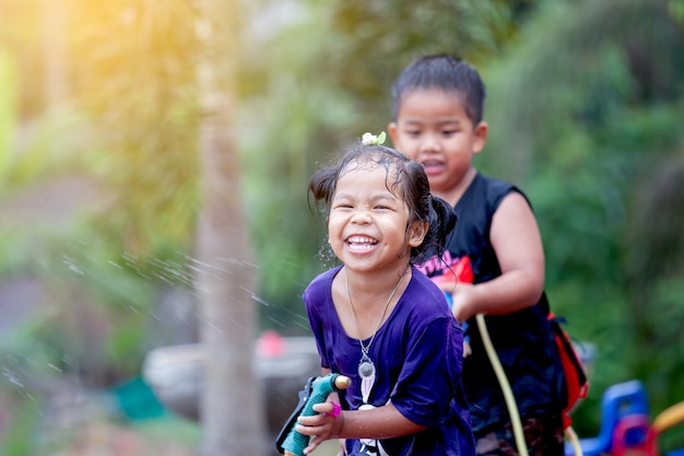 Enfants asiatiques s'amuser jouant avec de l'eau ensemble à songkran festival en thaïlande