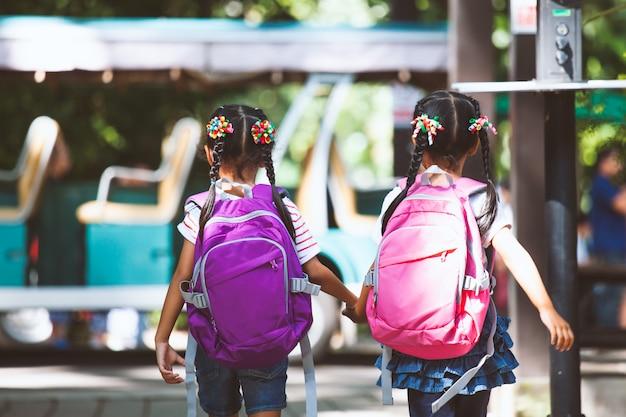 Enfants asiatiques avec sac à dos, tenant la main et aller à l'école avec autobus scolaire ensemble