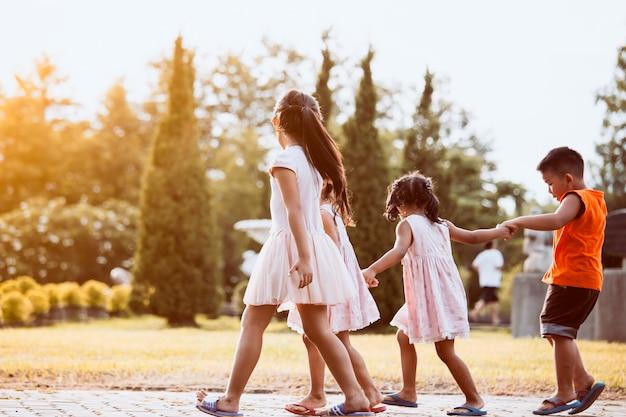 Enfants asiatiques, tenant la main et marcher ensemble dans le parc dans le ton de couleur vintage