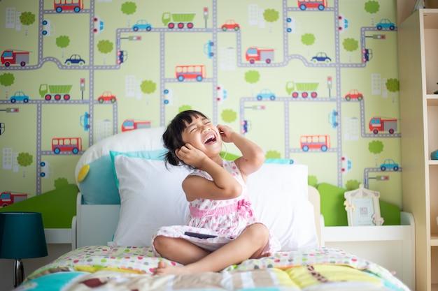Enfants asiatiques utilisant un casque pour écouter de la musique avec un smartphone sur le lit dans sa chambre décorée