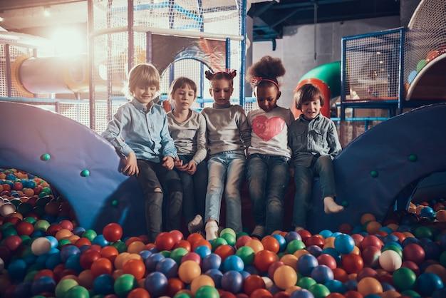 Enfants assis dans la piscine pleine de balles colorées