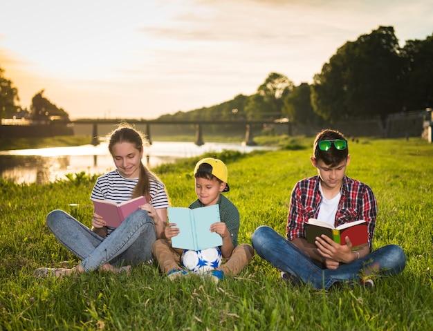Enfants assis sur l'herbe avec des livres dans le parc au coucher du soleil. journée d'été ensoleillée