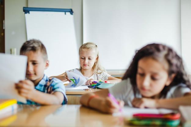 Les enfants assis en salle de classe étudient