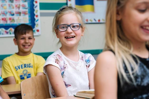 Enfants assis en salle de classe en souriant