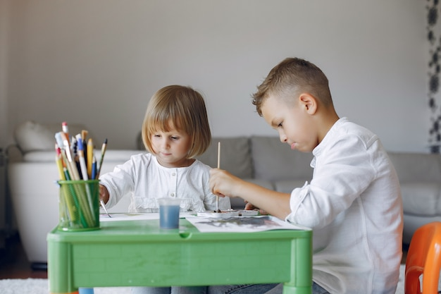 Enfants assis à la table verte et dessinant