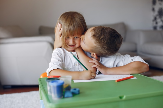 Enfants assis à la table verte et dessinant