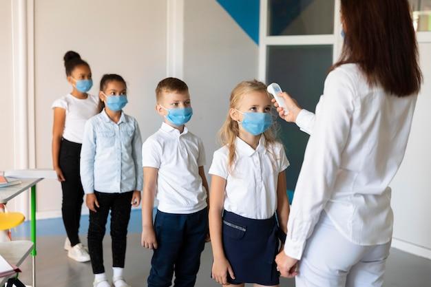 Les enfants attendent en ligne pour les mesures de température