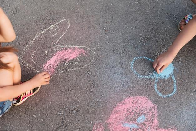Enfants au grand angle faisant des dessins à la craie