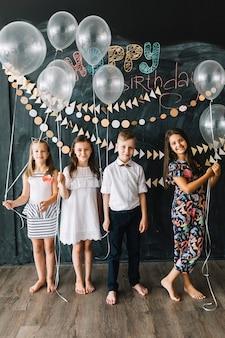 Enfants aux pieds nus avec des ballons lors d'une fête d'anniversaire