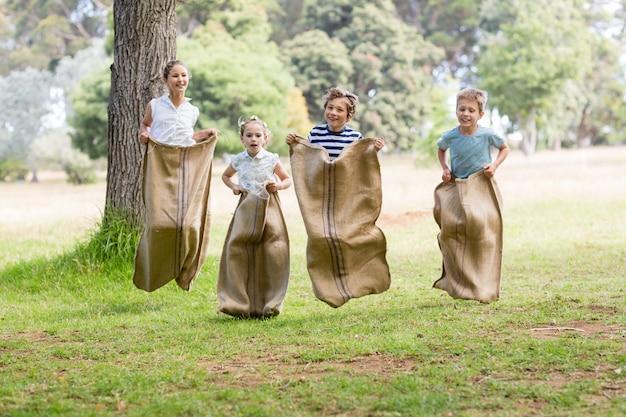 Enfants ayant une course en sac dans le parc