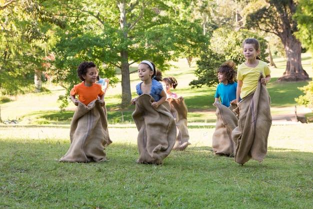 Enfants ayant une course de sac dans le parc
