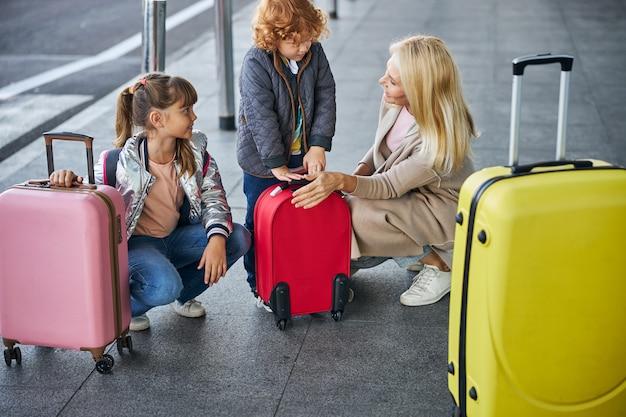 Enfants avec des bagages regardant leur mère