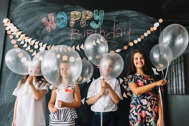 Enfants avec des ballons à la fête d'anniversaire
