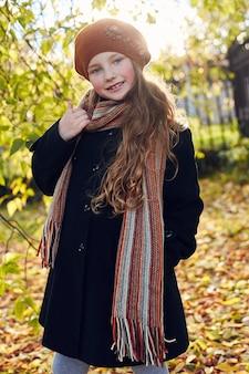 Enfants bébé en vêtements de printemps automne rétro. petit enfant assis souriant dans la nature, écharpe autour du cou, temps frais. des émotions vives sur son visage. ,