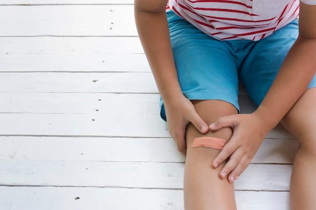 Les enfants blessés ou le garçon a eu un accident assis sur un fond blanc en bois.