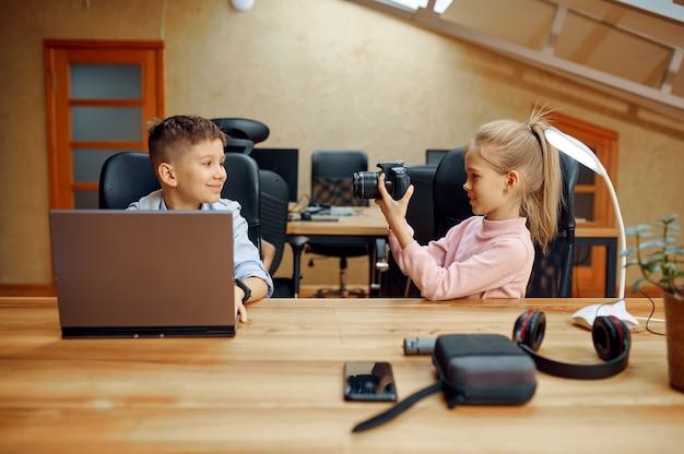 Les enfants blogueurs tirent sur la caméra pour le blog. enfants bloguant en home studio, médias sociaux pour jeune public, diffusion internet en ligne