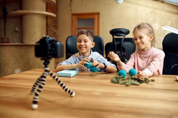 Les enfants blogueurs tirent sur la caméra pour le blog. enfants bloguant en home studio, médias sociaux pour jeune public, diffusion en ligne