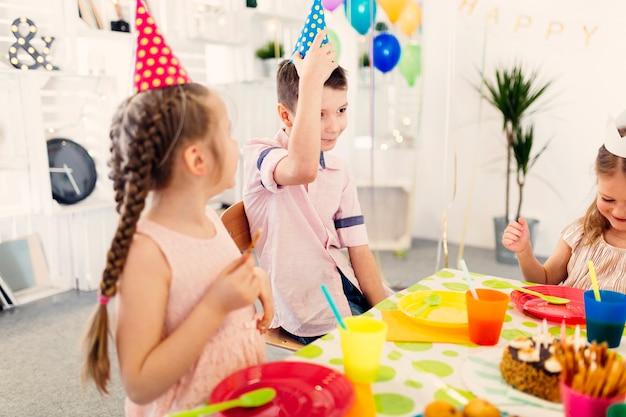 Enfants en bonnet de couleur assis à table