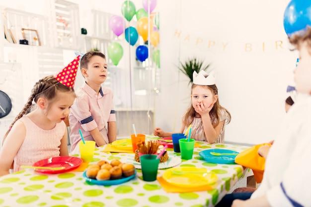 Enfants en bonnets colorés, assis à une table