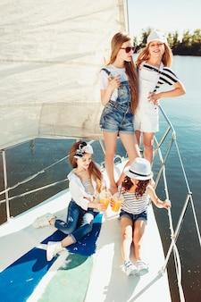 Les enfants à bord du yacht de mer buvant du jus d'orange. les filles adolescentes ou enfants contre le ciel bleu en plein air.
