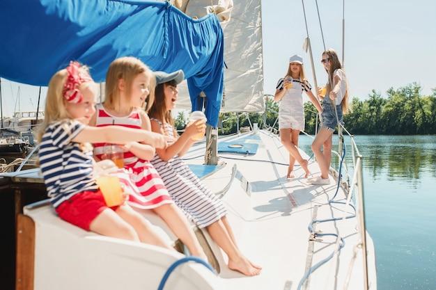 Les enfants à bord du yacht de mer buvant du jus d'orange