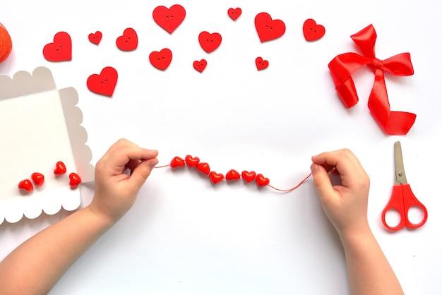 Les enfants de bricolage manipulent des coeurs de perles rouges sur une chaîne pour le bracelet de la saint-valentin. décoration de bébé à la main. concept d'artisanat.