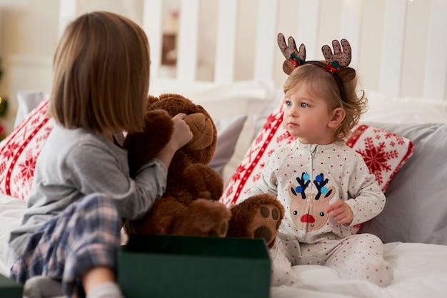 Enfants avec cadeau dans le lit