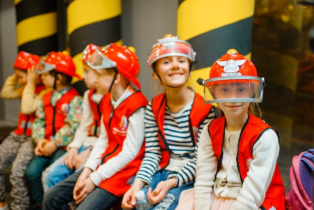 Enfants en casques et uniforme jouant au pompier