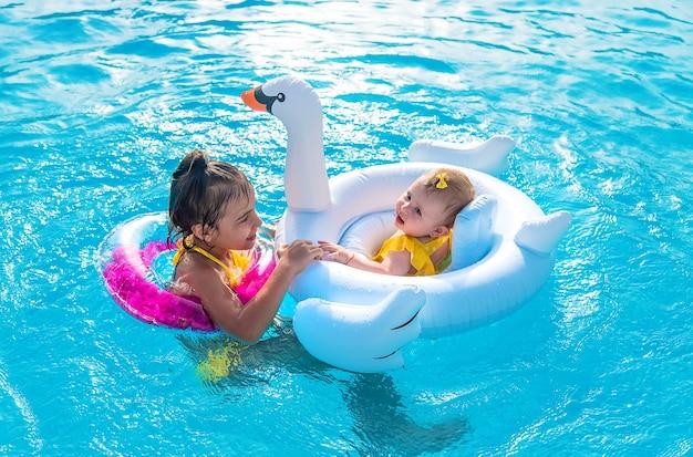 Des enfants en cercle flottent dans la mer.