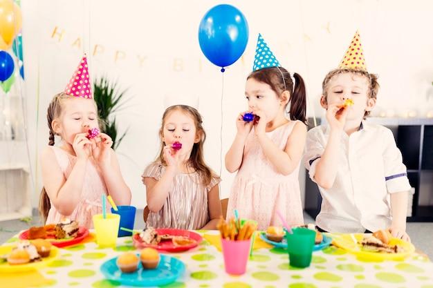 Enfants en chapeaux colorés sur la fête