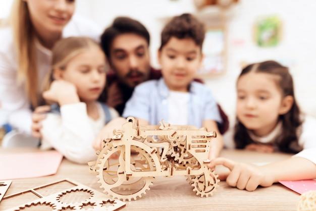Les enfants collectionnent un puzzle en 3d - un tracteur.