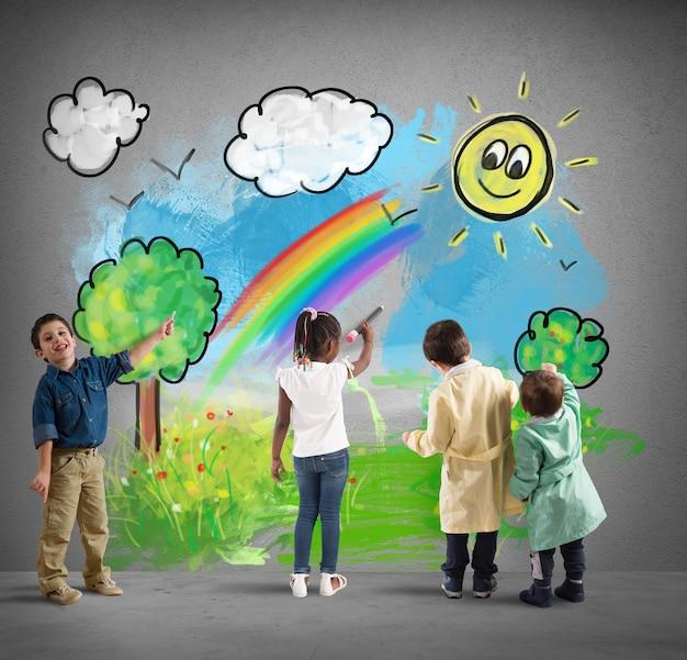 Les enfants colorent un paysage ensoleillé sur un mur gris avec des nuages