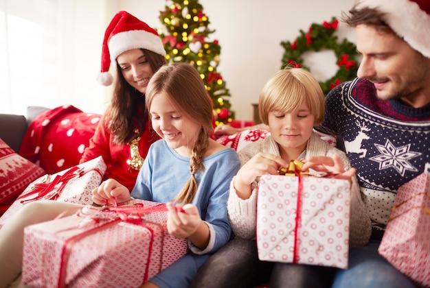 Les enfants commencent à ouvrir les cadeaux de noël