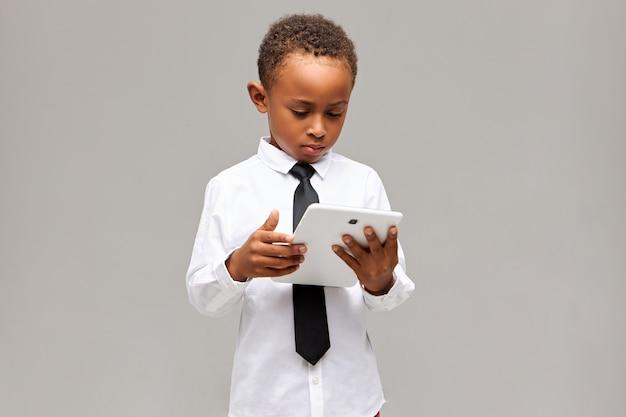 Enfants et concept de technologie moderne. écolier afro-américain sérieusement concentré en uniforme tenant une tablette numérique générique blanche, jouant à un jeu en ligne ou à l'apprentissage, ayant une expression concentrée