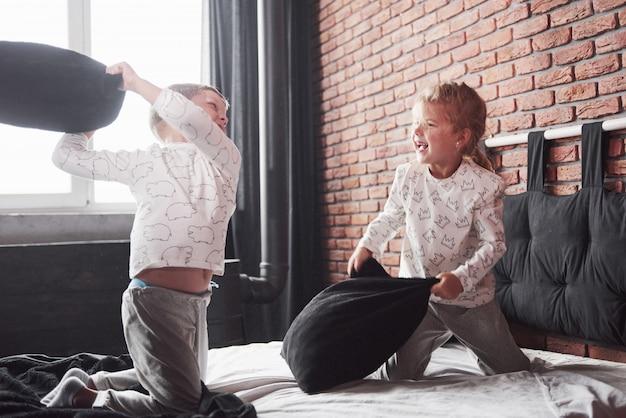 Enfants coquins un petit garçon et une fille ont organisé une bataille d'oreillers sur le lit de la chambre. ils aiment ce genre de jeu
