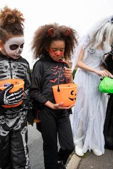 Enfants en costumes allant tromper ou traiter