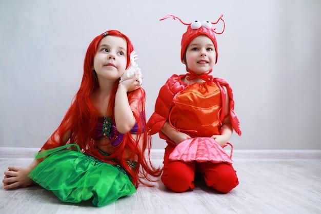Enfants en costumes de carnaval intelligents sur fond uni costume de créatures féeriques de la mer