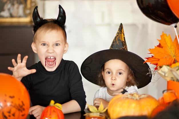 Enfants en costumes de sorcière et de diable pour halloween