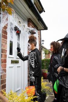 Des enfants en costumes trompent ou traitent chez quelqu'un