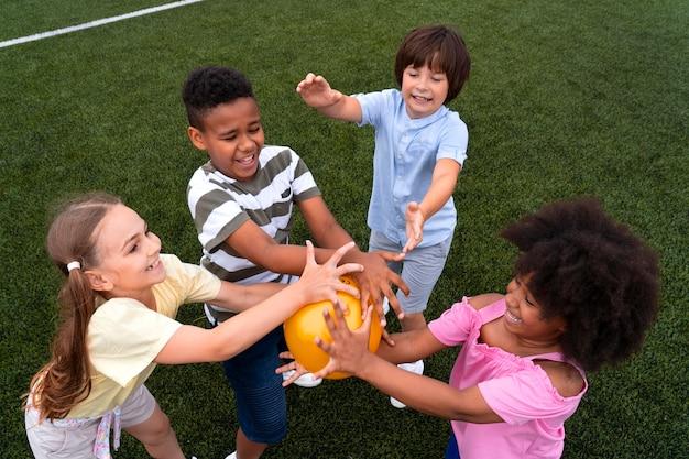 Enfants de coup moyen tenant des ballons
