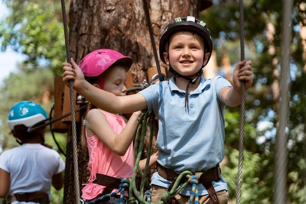 Enfants courageux jouant dans un parc d'aventure
