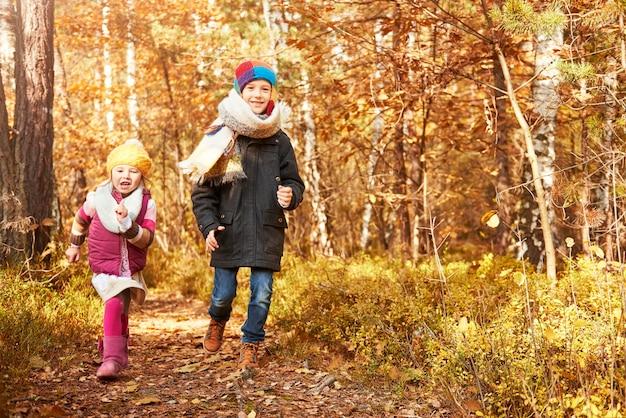 Enfants courant à travers le chemin forestier
