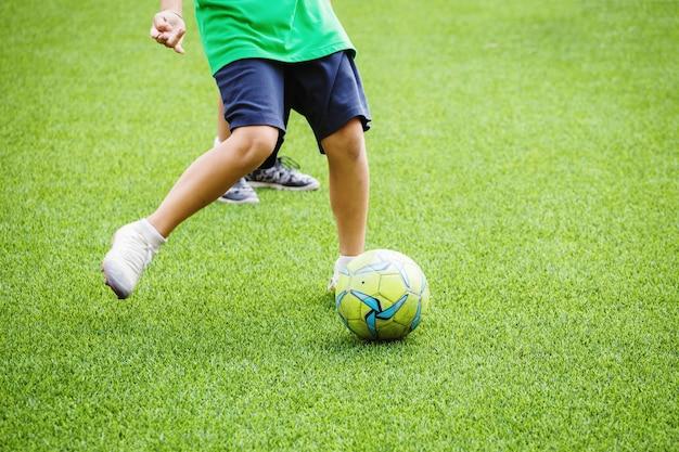Enfants courir et donner un coup de pied au ballon de football