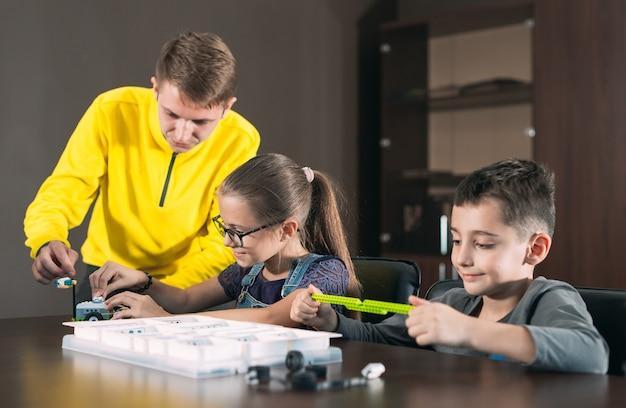Enfants créant des robots avec un enseignant. développement précoce, bricolage, innovation, technologie moderne.