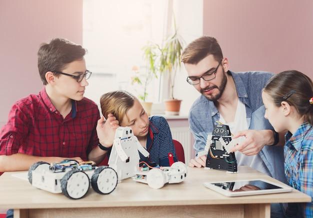 Enfants créant des robots avec un enseignant