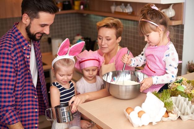 Enfants cuisinant sous l'œil vigilant des parents