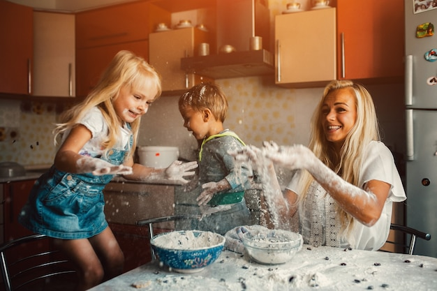 Enfants cuisine avec leur mère et de jeter la farine